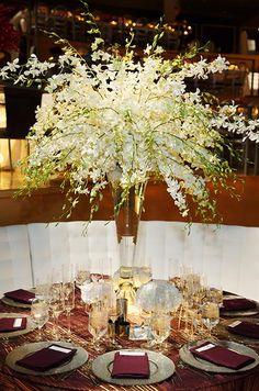 White dendrobium orchids juxtapose deep purple linens, creating a dynamic and elegant wedding reception table. #WeddingCenterpieces