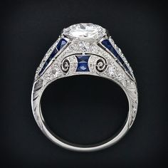Side view: Art Deco diamond and sapphire ring, circa 1925. This ring highlights a bright-white and shining European-cut diamond, accompanied with a G.I.A. Gem Trade Laboratory certificate stating: G color - VS1 clarity. The ring co-stars a magnificent and consummately sculpted Art Deco mounting ornamented all around with decorative open work, striking royal blue faceted calibre sapphires, sparkling single-cut diamonds and with hand engraving.
