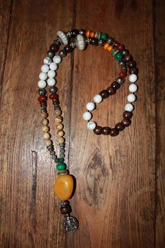 Necklace with white turquoise stone beads, picture stone beads, brown wooden beads, green glass beads, boddhi seeds,malachite stone beads, yak bone beads, tibetan silver spacer beads, tibetan silver capped white resin beads, one amber bead & a metal ganesh amulet pendant. 40 € (4)