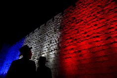 Monuments Around the World Light Up With the Colors of the French Flag After Paris Attacks - Two ultra-Orthodox Jews look at Jerusalem's Old City walls illuminated by the colors of the French national flag in solidarity with France after attacks in Paris, in Jerusalem, on November 15, 2015.
