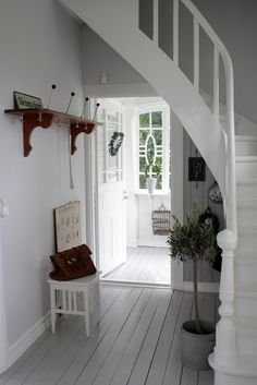 All-white tiny house foyer with stairs and handrail (site in Swedish).   Tiny Homes