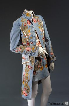 Ensemble | Roberto Cavalli (1940- ) | Italy 2002-2003 | Light blue embroidered denim and printed silk crepe-de-chine | In this ensemble, Roberto Cavalli references the suit of an 18th-century aristocrat with a redingote-style jacket and lavish floral embroidery. Cavalli contrasts this allusion to opulence with humble denim fabric, one of his signature materials, and a sexy micro-mini skirt | Bold combinations of various influences create a single cohesive look | The Museum at FIT