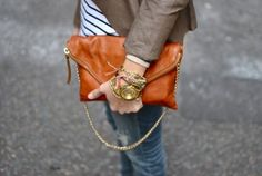 love the soft leather purse with chain handle, and love the combo of lots of delicate bracelets and big gold men's watch.