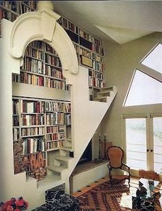 16 floor-to-ceiling bookshelves for decorating inspiration. This elegant living room bookshelf has its own archway and staircase, with a fireplace tucked underneath.