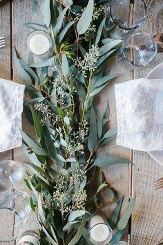 Australian Christmas table setting - linen napkins, gum leaf runner & plain white candles