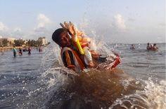 Um devoto carrega um ídolo do deus hindu Ganesh, divindade da prosperidade, no Mar Arábico, no segundo dia de Ganesh Chaturthi festival em Mumbai