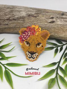 Tissage de perles en verre Miyuki. Une jolie tête de lionne couronnée de fleurs... Pour toutes les amoureuses de félins! La chaîne est en laiton argentée, garantie sans nickel, sans cadnium et sans plomb. Possibilité de la monter en pin's.