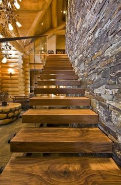 LOVE everything about this for our stairs to future mater loft. Full wall of faux stone, floating stairs and glass instead of railings