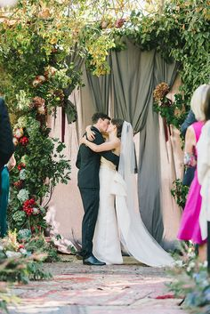 Grey draped fabric and arbor of oak branches, protea, hydrangea and lipstick pods make a beautiful ceremony backdrop