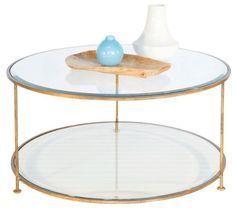 This lovely coffee table features a round design with two tiers. The table comes in a gold leaf finish with beveled glass tops. The table measures 36
