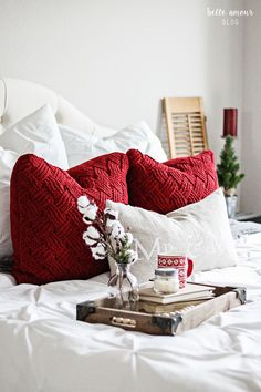 A simple yet cozy Christmas master bedroom with bright whites, deep reds, warm wood and festive greenery.