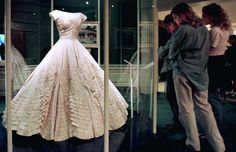 From Jackie Kennedy's wedding dress to the Playboy Bunny suit: the forgotten history of black American designers. Visitors to the John F. Kennedy Library Museum admire Jacqueline Bouvier Kenndey's wedding dress in Boston, May 27.  John F. Kennedy Jr. and his sister Caroline donated the dress to the museum after their mother's death.  The dress is made of over 50 yards of ivory silk taffeta. - RTXHHRH