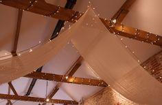 Flat muslin beam drapes with pealights for a rustic barn wedding at Upwaltham Barns by www.stressfreehire.com #venuetransformers