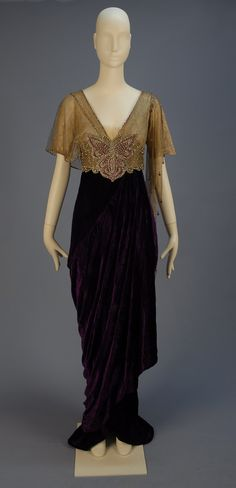 TRAINED VELVET BELLE EPOCH GOWN with JEWELED BODICE 1913. Lush royal purple panne silk having short sleeve silk lace V-neck bodice asymmetrically draped in gold metallic mesh, high jeweled midriff band with center clear and magenta paste butterfly, hobble skirt layered over short train.