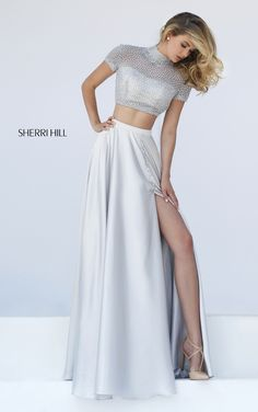 Flowing satin creates a classically feminine A-line silhouette in the Sherri Hill 50037 two-piece prom dress. The slightly curved crop top has a sheer beaded overlay, creating an illusion high collar neckline framed with illusion short sleeves. The full illusion back showcases a charming cutout. A sleek band accentuates the waistline of the long skirt as it cascades into a glorious sweep train. Covered buttons accent the skirt above the mid-thigh center slit.
