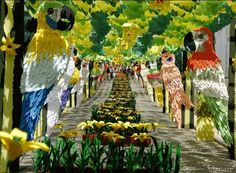 THIS IS A PAPER FESTIVAL IN PORTUGAL.         THIS IS BEAUTIFUL.    IT REMINDS ME OF THE ROSE BOWL PARADE.    THERE IS SUCH INTRICATE DESIGN AND VIVID COLOR.    I LIKE THE PARROTS AND THE FLOWERS.    I WOULDN'T LIKE THE PAPER CUTS    I WOULD ACQUIRE MAKING THEM