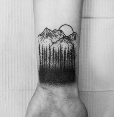 Tattoo on the wrist of the guy - the mountains and the woods
