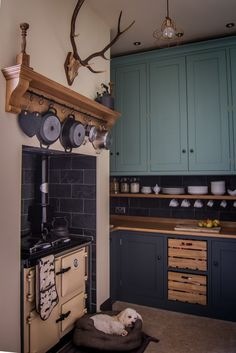 Sustainable Kitchens - Cotswold Chapel Kitchen. Tall oak wall cabinets painted in Farrow & Ball Chappell Green sit in this impressive converted chapel. Base cabinets contrast perfectly in Farrow & Ball Down Pipe. Oak worktops and shelving attached to slate wall tiles marry perfectly with the limestone flooring. The Rayburn range has tray slots built on the side. Toffee the dog enjoys the warmth while Steve the antlers watches over.