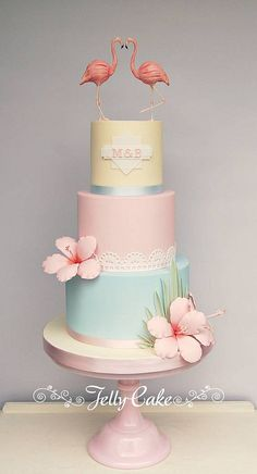 """This is one of the cakes I designed for the Squires Exhibition this year. It was inspired by the beautiful Luna invitation created by the amazing Paperknots, with a nod to the art deco """"American Riviera"""" in Miami.  Each tier iced in pastel colours with sugar palm fronds and hibiscus flowers on the base tier, hand cut lace to match the invitation around the middle and the top tier features a monogram, again taken from the invitation. Topped off with hand modelled flamingos."""
