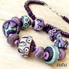 Beads by Verundela, via Flickr-especially the purple flattened rounds with the highlighted lined