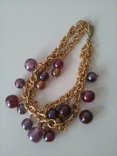 Bracciale in catenina color oro e pietre blu, viola e rosso scuro.