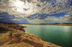 Lake Powell is a reservoir on the Colorado River, straddling the border between Utah and Arizona (most of it, along with Rainbow Bridge, is in Utah). It is a major vacation spot that around 2 million people visit every year. It is the second largest man-made reservoir, by maximum water capacity, in the United States behind Lake Mead, storing 24,322,000 acre feet (3.0001×1010 m3) of water when full. Lake Powell was...