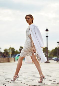 Just The Design:Kristina Bazan is wearing a white lace dress from and matching shoes from Elie Saab and the coat is fromChloé