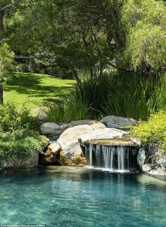 A waterfall off to the side completes the serene landscape of the pool area, placed into s...