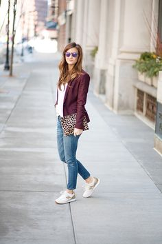 Cute outfits with sneakers: burgundy/wine blazer, white blouse, medium wash jeans, leopard clutch, and gold sneakers