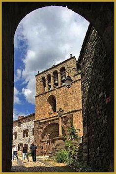 Photo au mois de juillet sous le grand portail d'entrée dans le coeur historique du village médiéval d'Arlempdes, face à la Croix en pierre du XVe siècle et à la façade orientale de l'église Saint-Pierre du XIIe siècle. Photos d'Arlempdes.