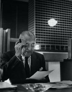 Mies, wearing glasses and reading, with model of new IBM building in background, ca. 1969–71. Image Courtesy of Chicago History Museum