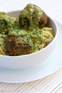 Bowl with vegan spinach balls with a pesto sauce on spagetti.