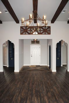 The entry to this home is fabulous! The beam work, vinyl plank flooring, arch ways, details, and colors used all make up this wonderful entrance into the living room of this light and bright home. We love to design!!