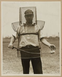 """1920's  'Photograph shows caddy Mozart Johnson wearing """"the latest safety device for golf courses"""" fashioned from wire-mesh and worn over the head and upper torso to protect """"caddies and ball-retrievers from wild golf balls.""""'"""