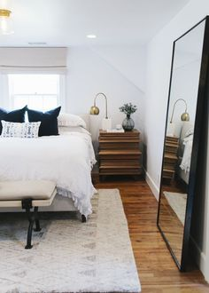 Modern bedroom featuring chic bedding, bench, rug with contemporary pattern, and a beautiful, oversized minimalist mirror.