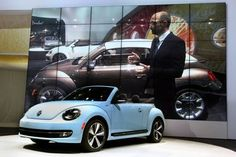 Klaus Bischoff, brand design chief for Volkswagen, stands next to the 1970's special edition toffee brown 2013 Beetle Convertible, on screen, at the L.A. Auto Show at the LA Convention Center in Los Angeles on November 28, 2012. In the foreground is the 1960's Denim Blue special edition Beetle convertible.