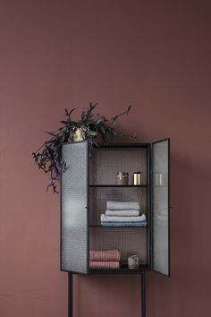 Opposites attract on this freestanding cabinet, carefully crafted from metal and wired glass