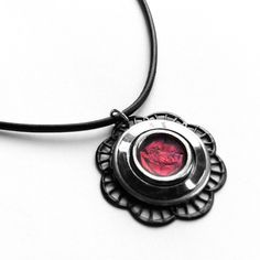 """A 1 1/8"""" diameter black metal filigree flower base layered with stainless steel and black silver plated metal surrounding a dark red and black marbled center. The marbling pattern on each necklace will vary slightly as the center color is not a stone, it is a metallic colored modeling material that is melted into each piece by hand."""