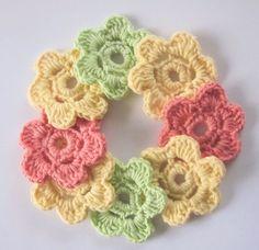 1 Sett med 8 hekla blomster, i gult, lakserosa og lys grønn.