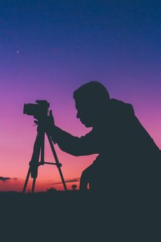 A silhouette of a photographer adjusting a camera on a tripod