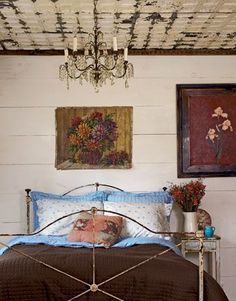 Rustic Feminine Bedroom. A tin ceiling from a New Orleans opera house and vintage chandelier add a sense of rustic glamour to this feminine room. Rich floral paintings and a chocolate brown bedspread add a touch of contrast.
