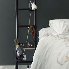 梯子をモチーフに、間接照明や本、小物などをかけて楽しむベッドサイド。クリエイティブな雰囲気が漂います。黒の壁と白のリネンの間にアクセントとなっています。