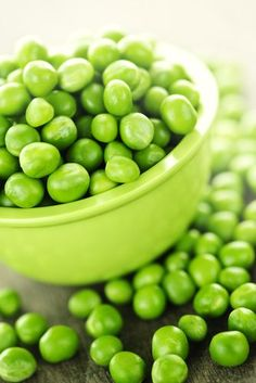 Fresh-shelled green peas in the same color of bowl. Photo by Elenathewise via Getty Images