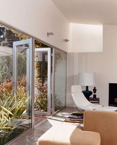 Seven-foot-high glass doors bring the garden, landscaped by Jay Griffith, into the living room. A skylight brings even more light into the white-walled room with polished-concrete floors. There is a splash of color in a custom rug designed by Dawn Farmer