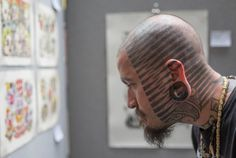 A man browses tattoo designs during the 10th International Tattoo Convention