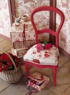 Chaise dont l'assise est recouverte de tissu fleuri et rebrodé de couleurs vives.
