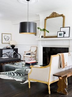 "Modern Classic Living Room  Combine modern and traditional design for a stunning space.   ""I love the architectural details of this living room,"" says Jen. ""The wainscotting, ornate ceiling medallion and colonial mantle all add interest to this living room. The mix of the new and old pieces of furniture adds a great deal of character too, even with the minimal colour palette.""  Take a video tour of this glamorous apartment, guided by Suzanne Dimma!  Photographer: Virginia MacDonald  Source…"