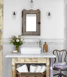 Sconces by Schoolhouse Electric flank a 1910 medicine cabinet, fitted with a new mirror, in this California ranch's guest bathroom. Bright idea: With the help of a marble top and a Kraus sink set, a weathered table became a washstand.   - CountryLiving.com