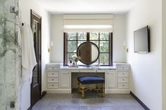 Elegant bathroom features a built-in makeup vanity paired with a royal blue velvet stool y illuminated by brass wall sconces tucked under a window dressed in a white roman shade. Bathroom Windows, Bathroom Rug Sets, Bathroom Furniture, Table Furniture, Furniture Design, Bathroom Goals, Mirror Bathroom, Bathroom Vanities, Kitchen Furniture