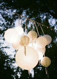 Romantische verlichte witte lampionnen op een tuinfeest. Verlicht ze ...